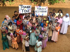 Children at Sirumalar Orphanage in Tamil Nadu, India hold up thank you signs for Punzo's restaurant.