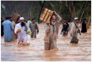 Residents and shopkeepers wade through a flooded street with their belongings after heavy rains in Peshawar on July 29. (Fayaz Aziz/Reuters - courtesy CBC.ca)