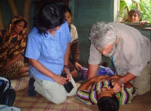 Dr. David Ratcliffe, CMAT Volunteer emergency physician from British Columbia, Canada treats 43 year-old Yusuf who is suffering from relapses of malaria. CMAT volunteer nurse and medical team member, Ms. Devi Crockford (a Malaysian Canadian) assists. Dr. Ratcliffe and other team members visited house to house treating people suffering from a wide range of maladies.