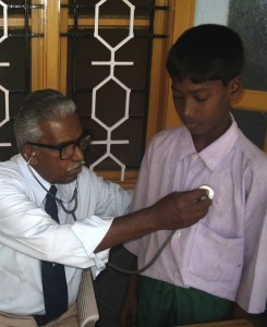 A young boy gets a checkup from a doctor in Sri Lanka.