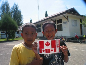 Happy Indonesian boys display Canadian flag stickers they received from our team. (January, 2005).