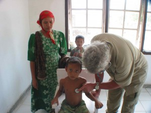 CMAT physician Dr. Dave Ratcliffe from Comox, B.C. assesses a child in Meuloboh, Indonesia (January, 2005)