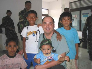 CMAT physician Dr. Darryl Leiski of Vancouver, B.C. poses with child survivors of the Tsunami in Meuloboh, Indonesia. The Indonesian Military (background) provided security for CMAT's  team in Indonesia (January 2005).