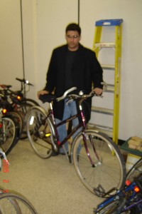 MacCycle director, Mr. Pradeep Singh stands with McMaster University President Mr. Peter George's donated bicycle.