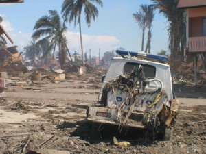 Tsunami devastation - Police vehicle badly damaged sits in Meuloboh street (January, 2005).