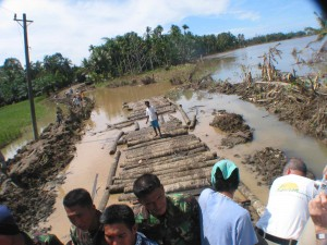 Tsunami devastation - Resilient Indonesian men in Meuloboh begin building a bridge into their devastated community. (January, 2005).