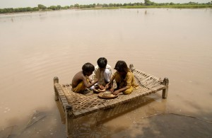 Displaced children play on a makeshift surface, after being displaced due to flood waters.