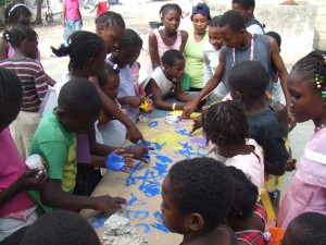 Children at an orphanage in Leogane prepare a thank you banner.