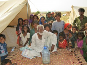 A family photo of Internally Displaced People (IDP) in a camp near where CMAT and IMAT will be working in southern Pakistan. Notice the colour of the drinking water in the bottle - it's the colour of tea with milk. Donations are needed to buy a large water purification unit.