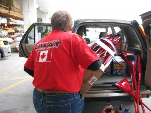 CMAT Volunteer Beth Clinton loads donated cleaning supplies into the car.