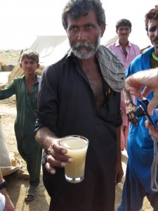 A displaced man shows the colour of the drinking water in the region. Donations are needed to buy a large water purification unit.