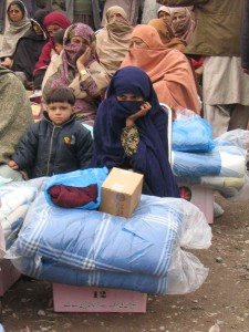 Women sit with relief supplies distributed to them by CMAT staff