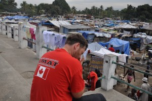A weary CMAT volunteer sits in the stadium stands, overlooking a displaced persons camp in Léogâne, Haiti. January 2010.