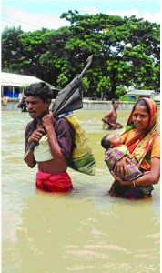 August 3, 2007: A couple with their baby moves to a safe place, wading through flood water.
