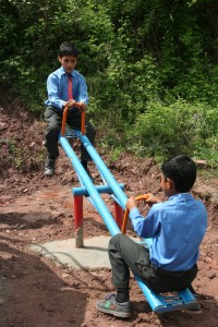 Boys play on the new see-saw installed on the grounds of their newly constructed school.