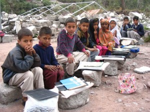 Children use the rubble of their collapsed school to study on.