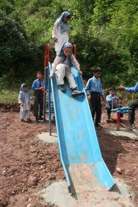 Young school girls enjoy playing on their new playground equipment.