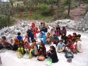 Kashmiri children sit in an outdoor classroom in the rubble of their former school. When weather is bad, the children don't attend school.