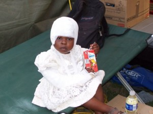 A little girl with a head injury and broken arm being treated at the CMAT Field Hospital in Leogane