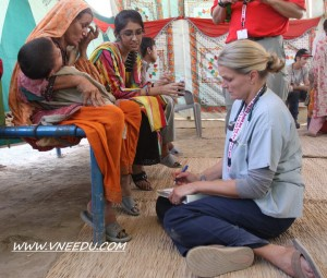 CMAT Team 2 - Through a translator, RN Keri Locke takes the history of a young child in Pakistan.