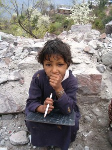 A little girl sits thoughtfully with her slate. Kashmiri children are resilient and are eager to study and learn.