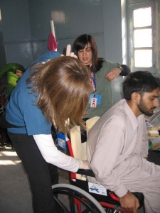 A.S. trying out custom back cushion made by CMAT rehab volunteers to accomodate spinal deformity.