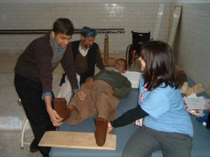Sarah coaching local P.T., Rajeesh on stretching techniques for B.A. (75 y/o from Muzaffarabad with incomplete spinal cord injury).