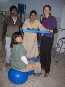 Joan & Sarah assisting E.J. (18 y/o from Bagh with incomplete spinal cord injury) as he stands (for the first time in 4 months) in standing frame.