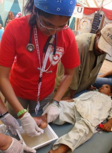 CMAT Volunteer Dr. Huma Ali cleans and dresses the foot of a young boy.