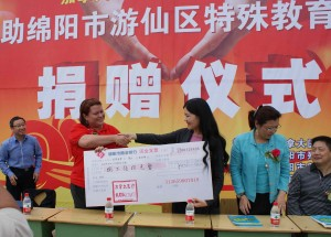 CMAT Executive Director Valerie Rzepka shakes hands and provides a donation of ¥85,000 RMB to Ms. Ma, Chairperson of Mianyang Municipal Handicapped Federation