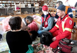CMAT physician Dr. Carl Jarvis, and paramedic Martin Metz assess and treat patients in an evacuation centre near Ishnomaki.