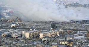 Smoke billows from an residential area in Sendai on March 12. (Photo Courtesy Kyodo News/AP)
