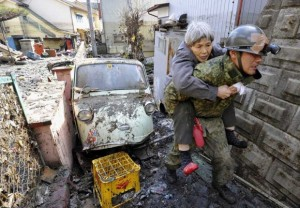 A stranded elderly woman is carried on the back of a Japanese soldier after being rescued from a residence at Kesennuma, northeastern Japan. (Photo Courtesy Kyodo News/AP)