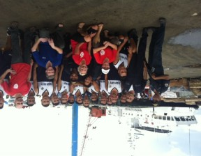 RN Teresa Burdesco. NP Kate Auger, and Paramedic Martin Metz collaborate with WHO, represented by Craig Hampton, working with the Philippine navy to offload and ensure delivery of IEKP kits.