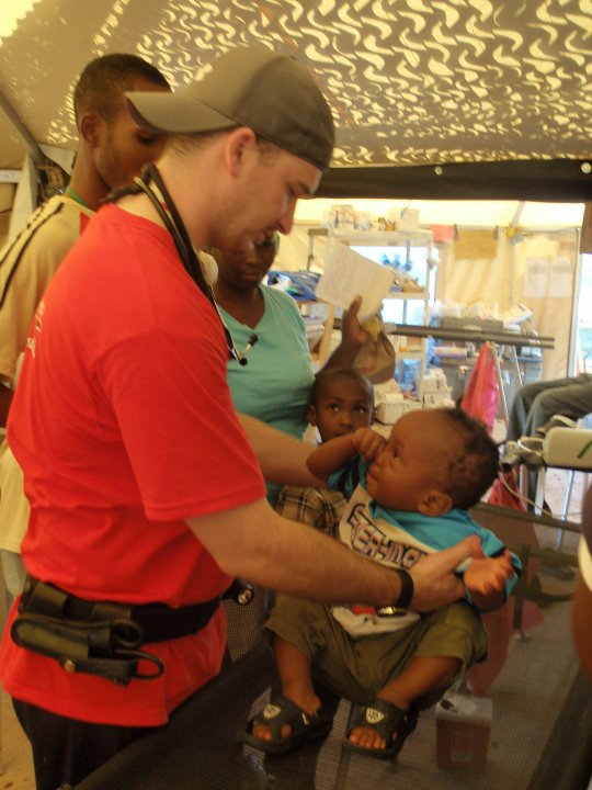 Brandon Duncan, RN assesses a small child in CMAT's field clinic in Pétionville, Haiti. April 2010.